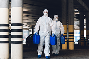 Covid-19, coronavirus, quarantine, medical workers in protective suits carrying barrels with disinfectant